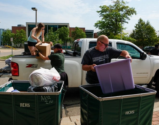 MSU sophomore Nialla Stepke hands a box to her mom, Amanda Stepke, as her grandpa, Ralph Ruelle, loads a cart Thursday, Aug. 26, 2021 at North Case Hall. Nialla took online courses at MSU all last year.