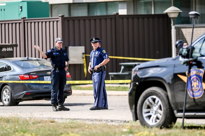 Michigan State Police investigate the scene of an incident on Thursday, Aug. 26, 2021, outside Sparrow St. Lawrence campus in Lansing,