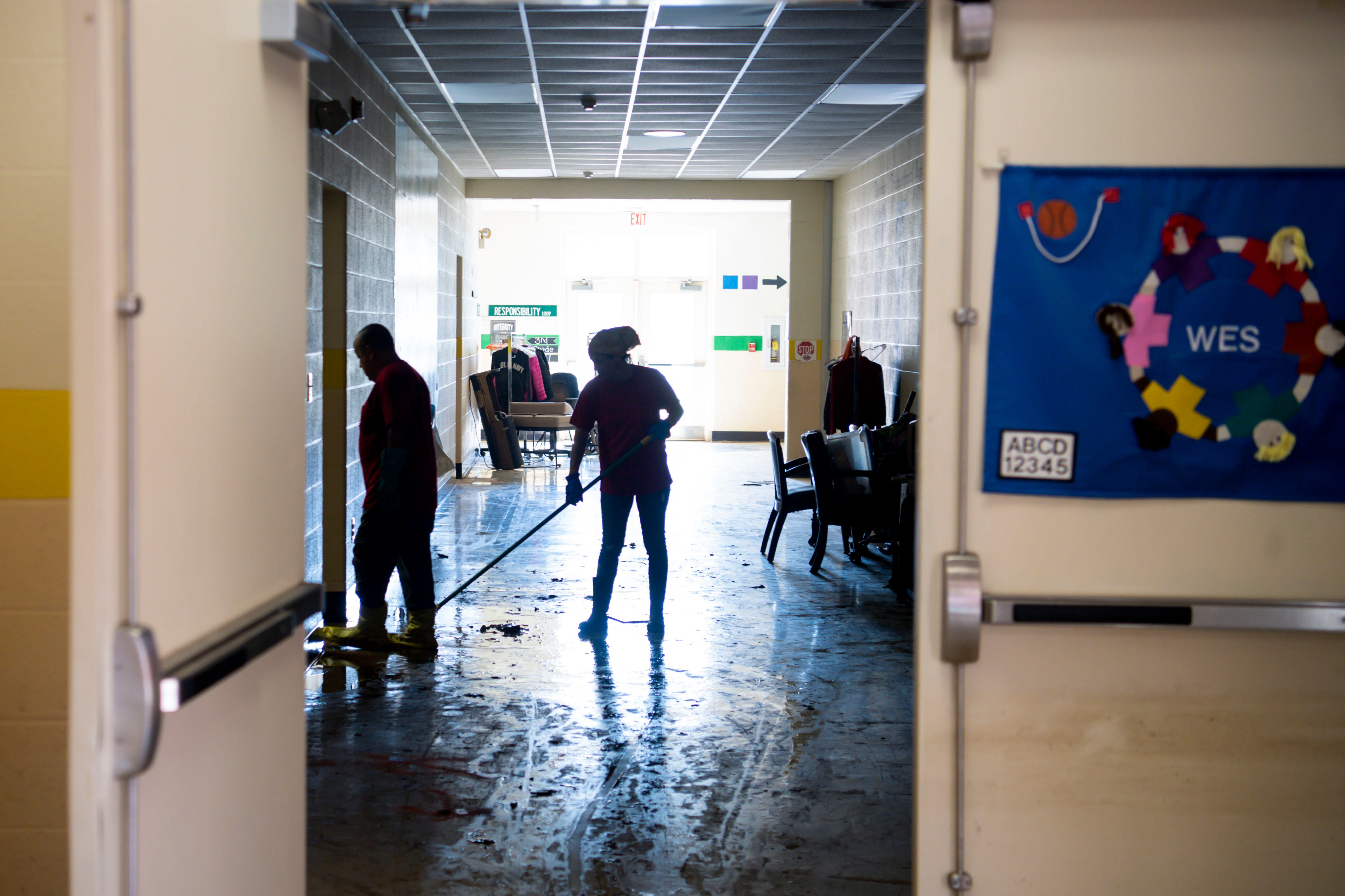 Clean up crew members are silhouetted in Waverly Elementary School Principal as they work on Wednesday, Aug. 25, 2021, after flash flooding swept through the town of Waverly, Tenn.