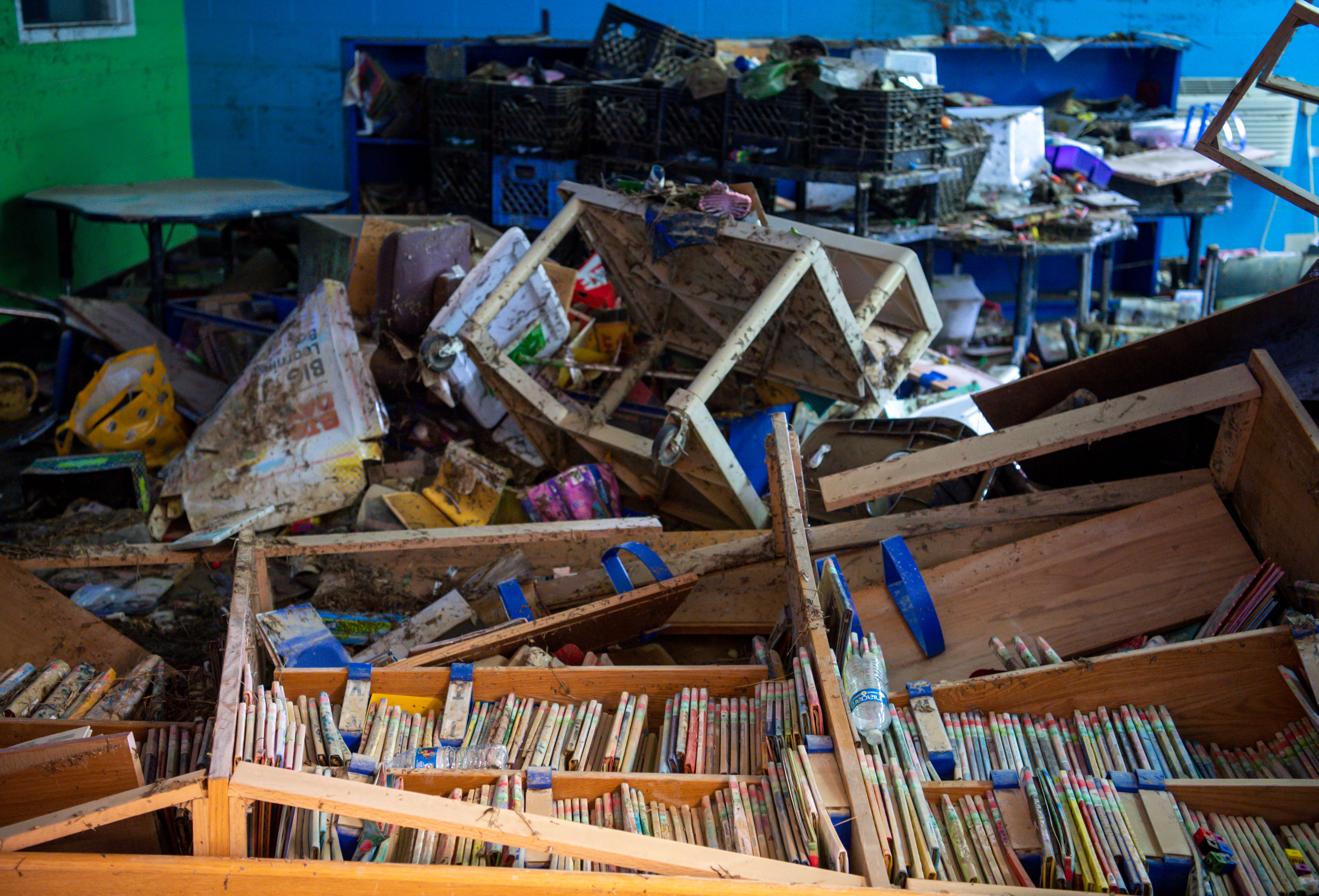 Bookcases are seen toppled over in the flooded Waverly Elementary School library as seen on Wednesday, Aug. 25, 2021, after flash flooding swept through the town of Waverly, Tenn.