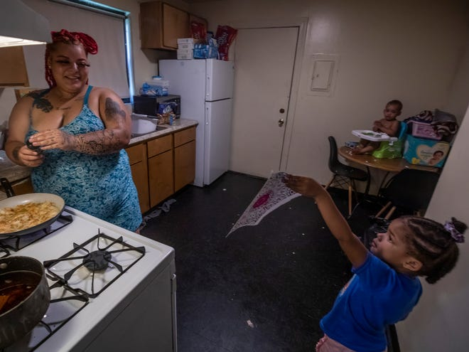 Lexus Ikeard, left, prepares a meal for her family and reacts as her daugher Armoniie Lawless shows her artwork at their residence in Nashville on Wednesday, August 25, 2021.