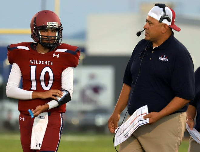 Wildcat quarterback Tony Aguilar and assistant coach Richard Perales meet on the sideline.
