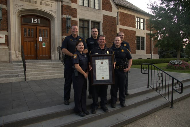 Birmingham Police Chief Mark Clemence holds an accreditation certificate.