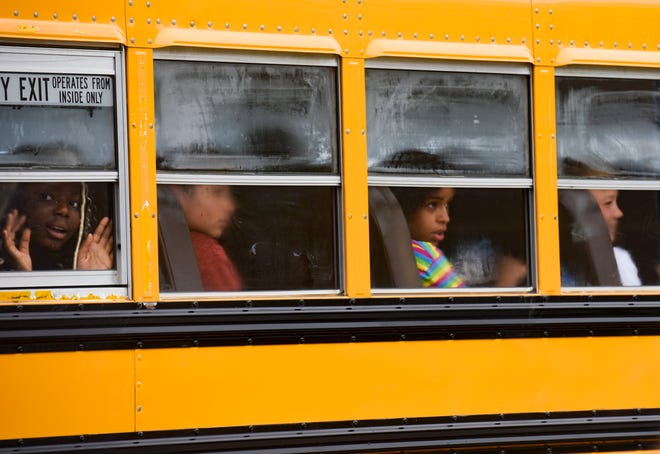 Students look out of foggy school bus windows as they arrive for the first day of school on Thursday, August 26, 2021 at the new Ben Reifel Middle School in Sioux Falls.