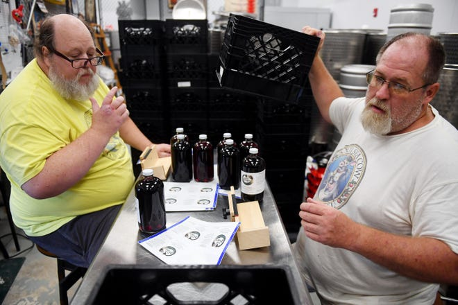Brothers Gregory (left) and Bryan Welling affix labels on bottles of mead, or honey wine, on Wednesday, Aug. 25, 2021, in their brewing space at Sunshine Kitchen in St. Lucie County. The brothers created Rabbit Hole Brew Station in March 2019 and have created three sub-brands within the company. Sour Sea Cow, focusing on sour hard ciders, Thirsty Dragon, which are specialty meads, and Vicious Vinegar. The brothers also have a plot of land where they plan to grow local fruits and herbs and have beehives.