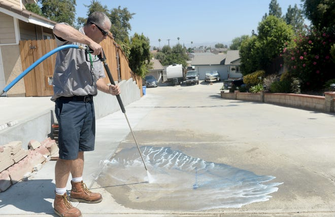 Brad Perry, community service technician with the city of Simi Valley cleans graffiti on Elizondo Avenue Thursday morning after an overnight vandalism incident marked garage doors, sidewalks and streets.