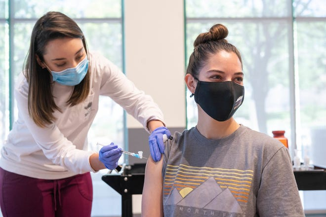 Bức ảnh này được cung cấp bởi Đại học Bang New Mexico cho thấy y tá Marissa Archuleta của Trung tâm Sức khỏe và Sức khỏe Aggie (trái) đang tiêm vắc-xin COVID-19 của Johnson & Johnson cho Lauren Naranjo tại một phòng khám tại Trung tâm Corbett ở Las Cruces, New Mexico.