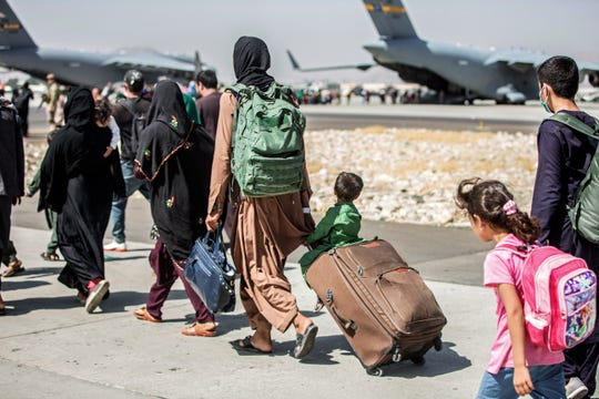 Families walk towards their flight during ongoing evacuations at Hamid Karzai International Airport, in Kabul, Afghanistan. A school district in a San Diego suburb that is home to a large refugee population says many of its families who had taken summer trips to Afghanistan to see their relatives have gotten stuck there with the chaos following the withdrawal of U.S. troops.