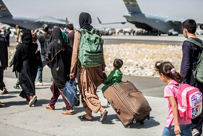 Families walk towards their flight during ongoing evacuations at Hamid Karzai International Airport, in Kabul, Afghanistan.