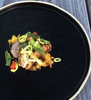 A dish of thin-sliced pork medallions topped with peppers and onions at The Kitchen at Southold Farm + Cellar.