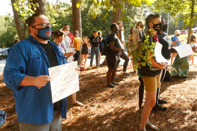 Demonstrators protest banning critical race theory in the classroom in front fo Brumby Hall on the campus of the University of Georgia in Athens, Ga., on Friday, Aug. 27, 2021. Brumby Hall was the site of Linnentown, a Black community that was forced out of their home via an urban renewal project lead by UGA and the City of Athens.