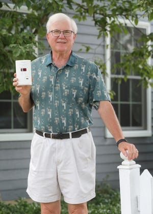 Tom Peltier holds his new Kidde Night Hawk carbon monoxide detector with a digital display on Friday at his Akron home.