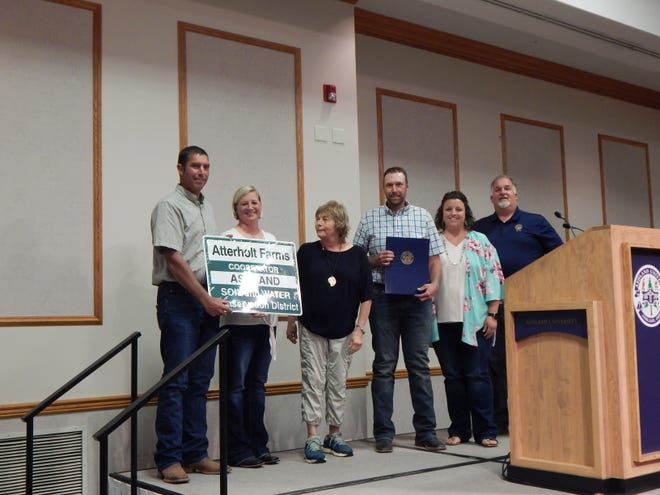 The Atterholt Farm was presented as the Cooperator of the Year with brothers Mike and Aaron accepting along with their wives Mandy and Mandy at their sides with Karen Welch and state Rep. Darrell Kick, R-Loudonville, presenting.