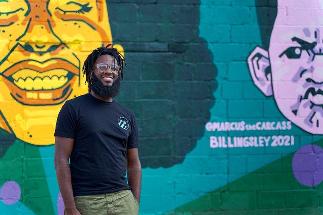 Marcus Billingsley in front of the mural he painted on the MadLab building Downtown.