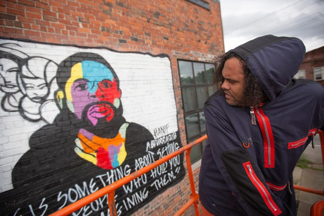 Local artist Bryan Moss moves back to look over his work on a mural featuring Hanif Abdurraqib along East Main Street.