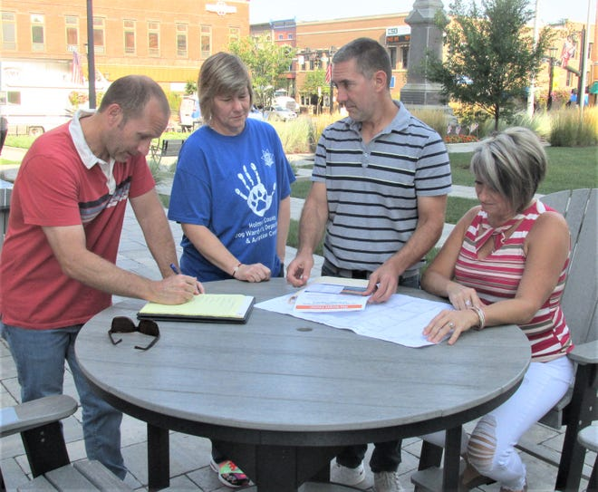 Mark Leininger, from left, Susan Schie, Arnie Oliver and Tracy Schlabach go over some notes and information about the Holmes County Comprehensive Plan which is in the works.