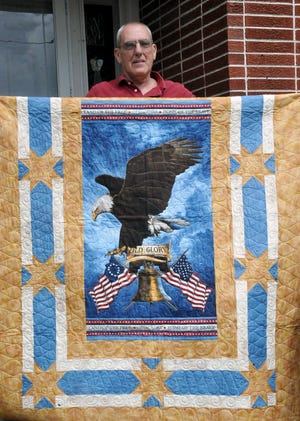 Joe Zehnder stands with the Quilt of Valor he received during the Orrville High School class of 1966 reunion. He was one of 23 quilt recipients. The project to honor the veterans was spearheaded by classmate Doranna Yung.