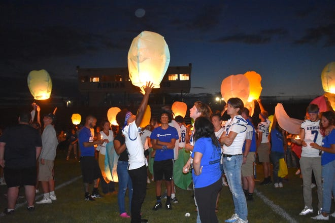 """Members of the Adrian High School varsity football team, friends, classmates and loved ones of Jacob """"Guzi"""" Guzman, 18, send floating lanterns off into the sky Thursday night during a candlelight vigil at Maple Stadium in Adrian for Guzman."""