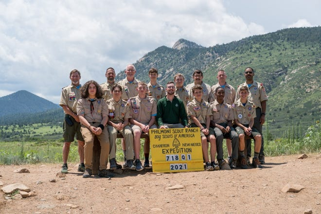 Expedition 718-Q-01 are pose for a photo with the Tooth of Time mountain in the background. Pictured front row, from left, are Ryan Rhoades, Rourke Solomonson, Cameron Brehmer, Philmont Guide Bradley Sykes, Thomas Belleau, Stephen Venerable and Andrew Rowe. Back row, from left, are John Solomonson, Ryan Rowe, Jeff Brehmer, Haeden Poore, Chris Thomas, Matt Thomas, John Poore and RaShawn Venerable.