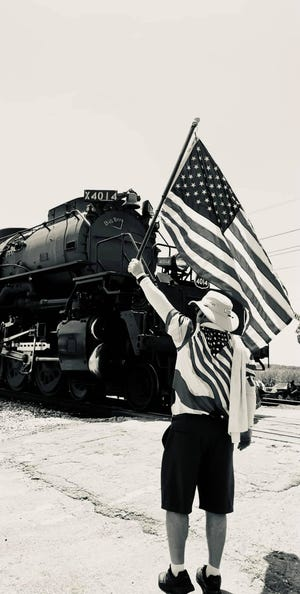 Maci Breaux captured a patriotic photo of a man holding a flag in front of the Union Pacific Big Boy 4014 when it stopped in Donaldsonville.