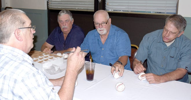 Tom Rathbun (left) tells a story while Keith Chrisman and Rick Grainer add their names to balls across the table during the signing session before dinner at the Little Falls Mounties' 1970 Section III baseball championship reunion dinner.