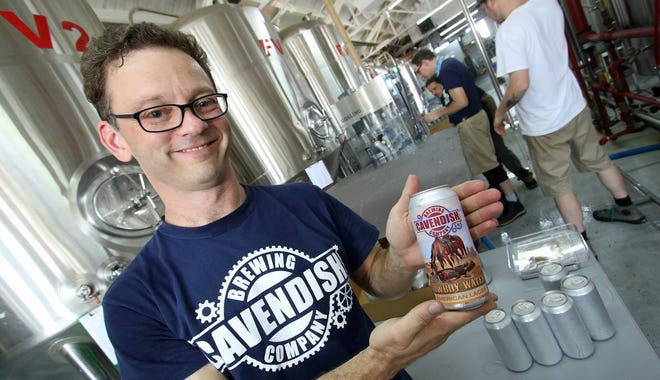 Owner, General Manager and Master Brewer Scott Cavendish holds a can of Cowboy Water American Lager just off the canning line at Cavendish Brewing Co. Friday afternoon, Aug. 27, 2021.
