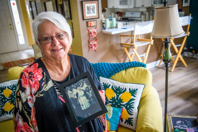 Cynthia Mosca poses in her home Aug. 26 with a picture of herself from her days in the Peace Corps in Ethiopia more than 50 years ago.
