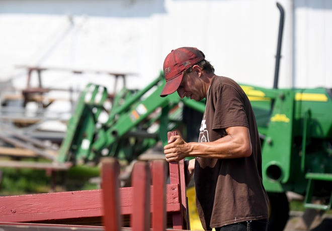 Mason Bair, groundskeeper at Stark County Fairgrounds, takes a count of benches as workers prepare for the return of the Stark County Fair. The fair runs from Tuesday to Sept. 6.