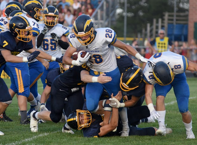 Luke Levicki of Ida grinds out a couple of yards as Kaden Kull, Nolan Zajac and others of Airport bring him down Thursday August 26, 2021.