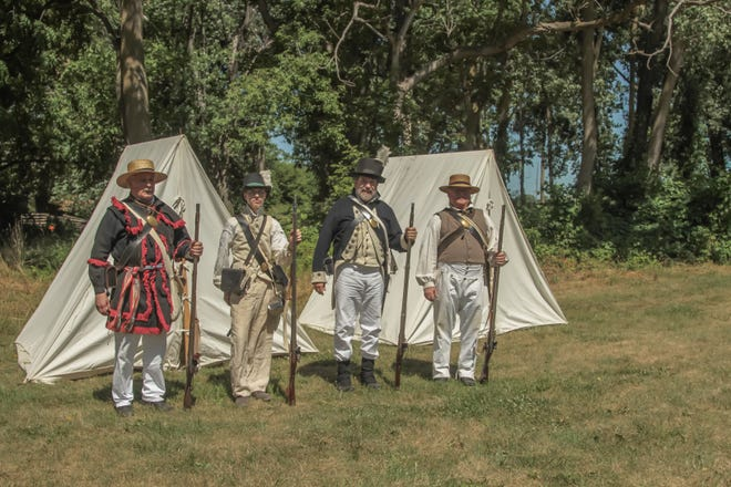 Members of the Lacroix Company of Michigan Volunteers of 1812 pose with their black powder muskets at the National Battlefield Park during black powder days in 2018.