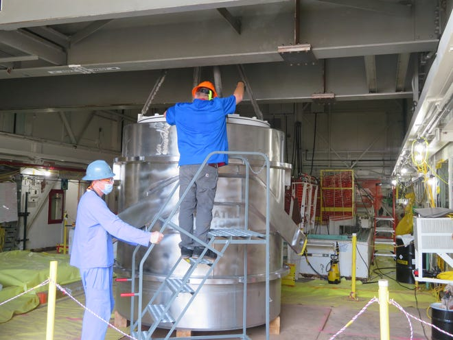 Employees at Oak Ridge place a waste disposal liner into an 88,000-pound transportation cask to safely ship irradiated materials from a reactor pool offsite for disposal.