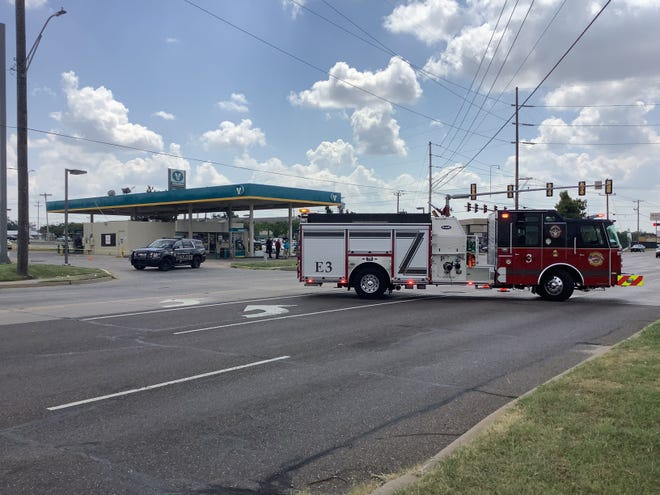 Emergency and police vehicles are parked outside the Valero gas station on the corner of Air Depot and Reno in Midwest City on noon Friday. The parking lot was the site of a police shooting Friday morning, after officers responded to reports of a man walking around the area firing his rifle into the air and refusing to drop his weapon.