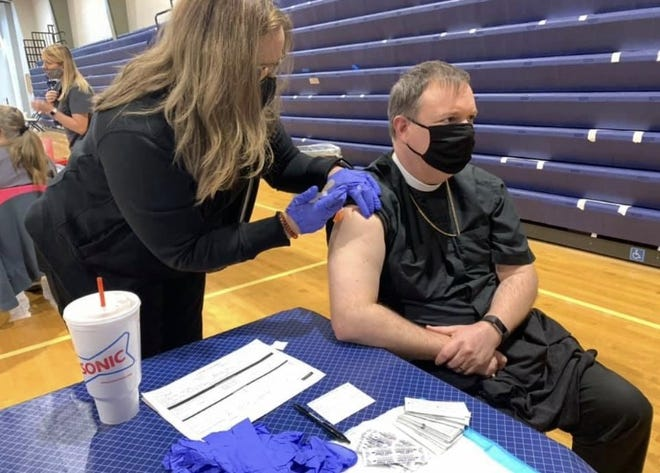 A health care worker vaccinates the Rt. Rev. Poulson Reed, bishop of the Episcopal Diocese of Oklahoma, during a COVID-19 vaccination clinic.