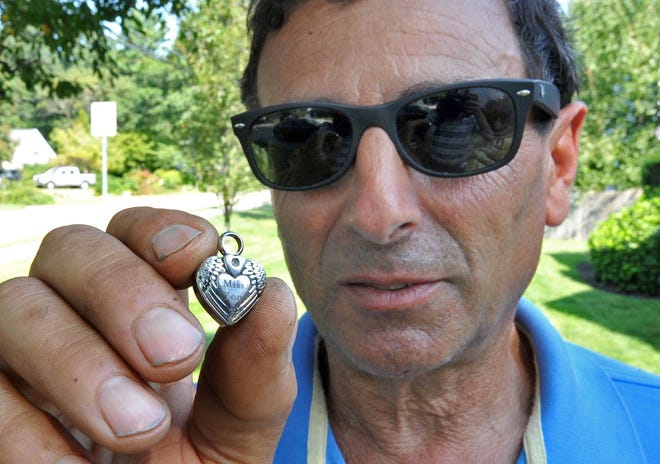 Rich Bonanno, of Scituate, holds a locket he found with his metal detector in the sand at Nantasket Beach in Hull recently and is reuniting it with its owner, Thomasina Holley-Lewis, Friday, Aug. 27, 2021.