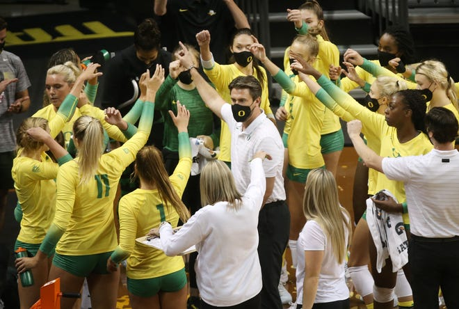 Oregon head volleyball coach Matt Ulmer, center, wraps up a court side meeting with his team during the Oregon Invitational.