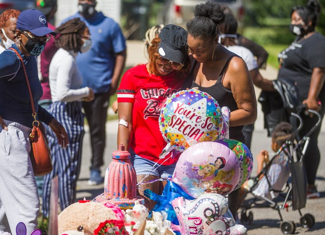 The mother of 7-year-old Chrisyah Stephens is comforted as she approaches a vigil Aug. 31, 2020, outside the home where Chrisyah was shot and killed in South Bend.