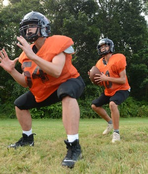 Plainfield quarterback Codey Leferve takes a snap from center Llogan Caron during practice in Plainfield.