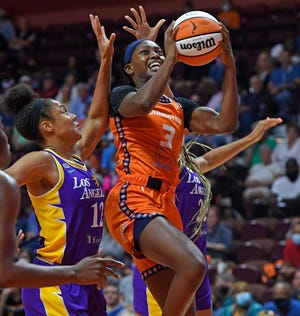 Connecticut Sun forward Kaila Charles splits the defense of Los Angeles Sparks guards Nia Coffey, left, and Arella Guirantes during the Sun's 76-72 win in Uncasville.