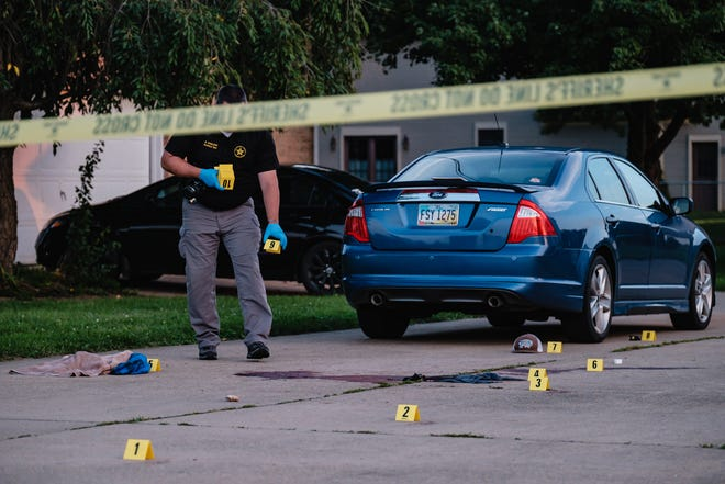 Evidence technician Sgt. Ryan Hamilton of the Tuscarawas County Sheriff's Office works Thursday evening at the scene of a shooting at 334 Third St. SW in Strasburg.