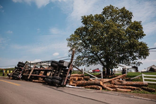 A logging truck driven by Urban Beachy of Beachy Trucking LTD, which overturned on state Route 93 in Sugarcreek, is attended to by emergency responders and recovery crews Friday, August 27 in Sugarcreek, Ohio.