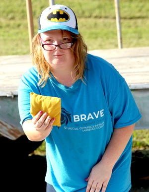 Special Olympics competitor Destiny Beavers participates in the Lawrence County Special Olympics Cornhole Tournament Thursday. The tournament was held at the Bedford Knights of Columbus parking lot. The Special Olympians have had corn toss practices at the parking lot every Thursday since July 8. They are looking to compete in the Special Olympics State Tournament held in Carmel this fall. To compete at the State Tourney, the athletes need to have at least eight practices.The Knights of Columbus have provided the the parking lot, and one of the members made the corn toss boards. There have been 6 Knights of Columbus members at all the practices, according to former Knights of Columbus Grand Knight Greg Stanley. Current Knights of Columbus Grand Knight Jon Nett says that the annual Tootsie Roll drive will kick off Sept. 10 and 11, with the proceeds benefiting the Lawrence County Special Olympics, as well as playground equipment for Parkview school, and LARC. Special Olympians will be offering the Tootsie Rolls at the Bedford Wal-Mart that weekend.