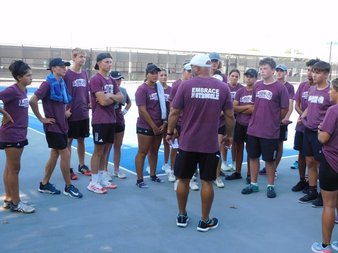 Ennis tennis head coach Keith Howard (center) Is surrounded by his varsity team following Tuesday's district match against Midlothian.