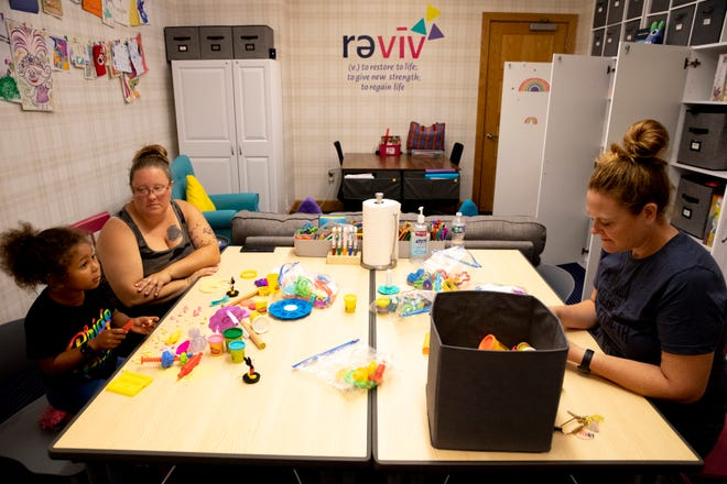 """Tricia Lusher, right, Reviv programs director, plays with play dough with Czarina Green, 4, of Westfield, Ind., and her mother, Brittany Hall, on Friday, Aug. 27, 2021, at Reviv in Cincinnati. Green was visiting Reviv Family Support Services in between appointments at Cincinnati Children's Hospital Medical Center. """"We can come here instead of sitting in the car in-between appointments,"""" Hall said. Reviv is a nonprofit that helps families with medically fragile children."""