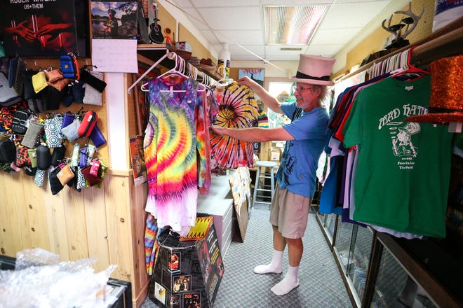 Mike Bigsby hangs tie-dyed shirts at his Mad Hatteur store, recently relocated at 459 S. Main St. in Fond du Lac.