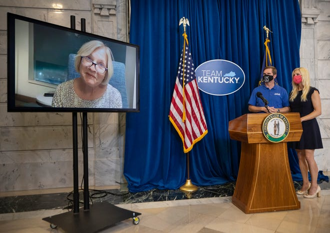 Kentucky Gov. Andy Beshear and his wife, Britainy, listen as the third and final Shot-at-a-Million winner, Mary Mattingly of Louisville, speaks via video at the state Capitol. Aug. 27, 2021