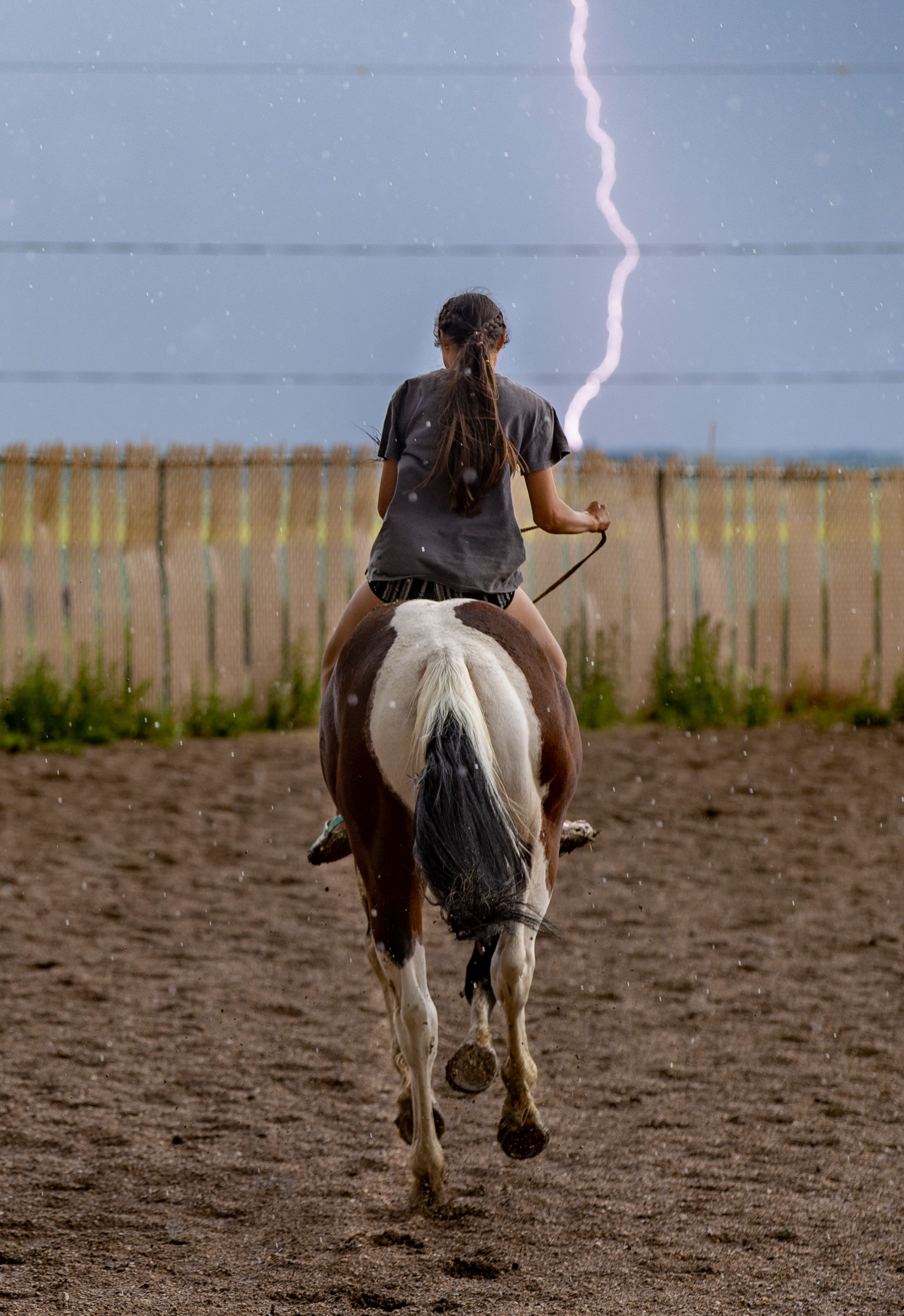 Lightning strikes as a young rider takes off on a horse at the Parshall Lucky-Mound Rodeo as a storm rolls in across the plains. June 26, 2021
