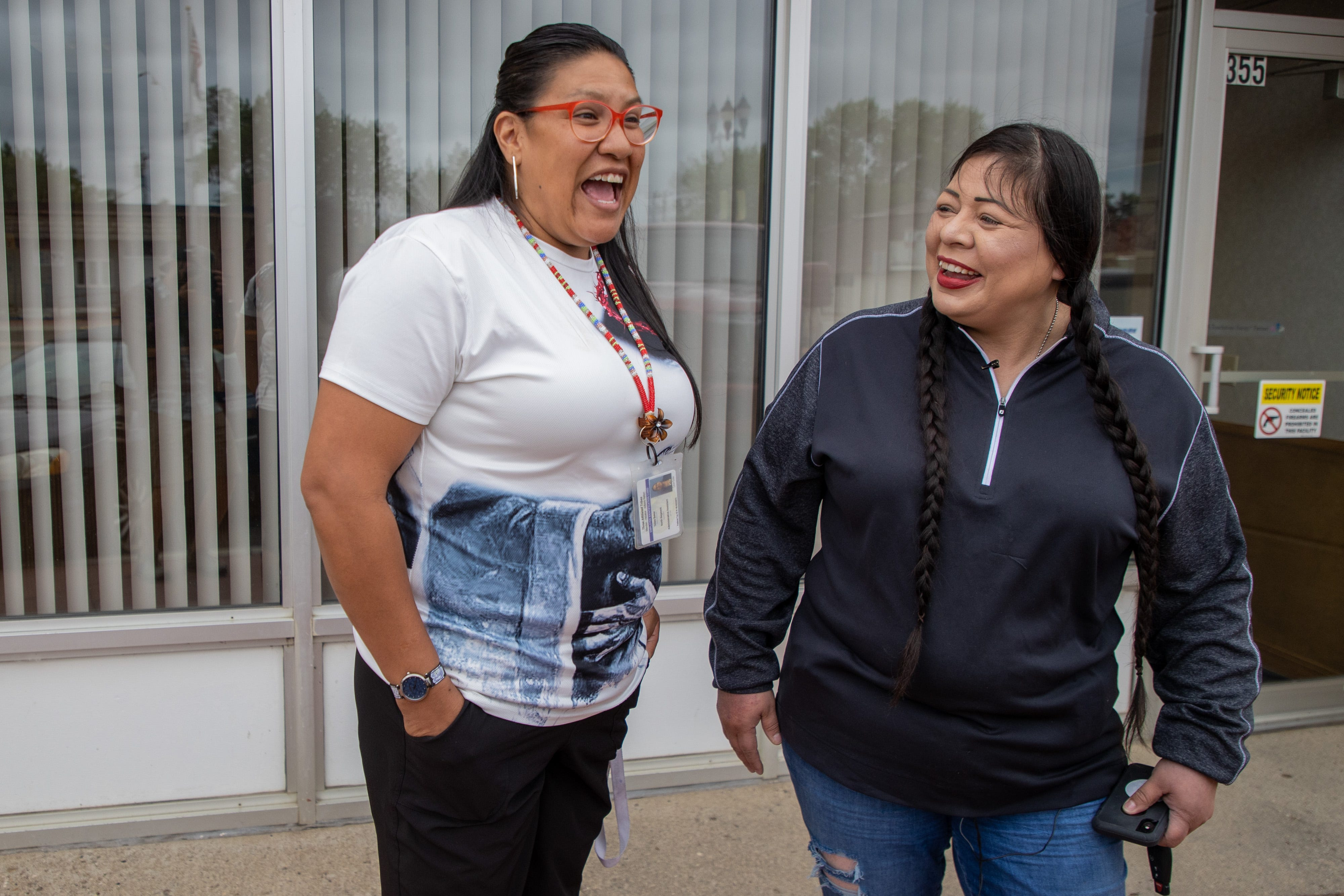 Fort Berthold Reservation resident Liea Baker, left, a former addict and current peer support specialist, has a laugh with her aunt, MHA Drug Enforcement special agent Dawn White, in downtown New Town, N.D.