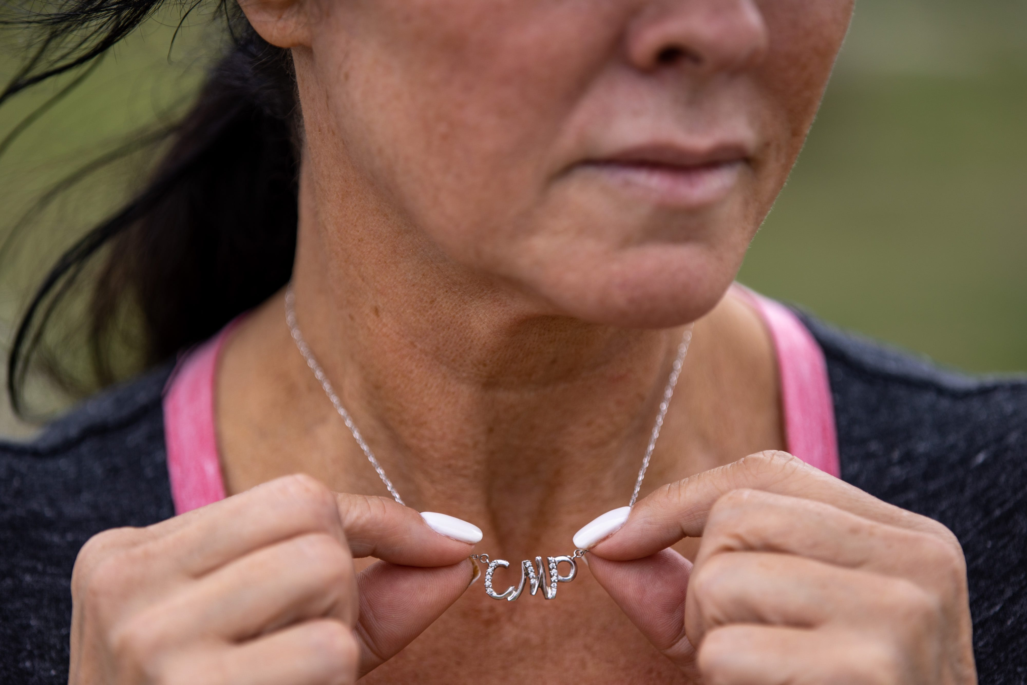 Rhonda Packineau wears a necklace with her daughter, Cheyenne Packineau's, initials as she visits her grave in the Parshall, North Dakota Meadows Cemetery. Cheyenne, a standout basketball player at Parshall High School who holds the all-time scoring record, began taking pain pills in high school to cope with a sports injury. Her abuse continued into college, where she got a full-ride scholarship for basketball. In 2018, she was found dead from an overdose of Fentanyl in a Bismarck hotel room at just 21 years old. Today, Cheyenne's family raises Cheyenne's son, Kasten, as they aim to raise awareness about addiction in their daughter's memory. June 26, 2021