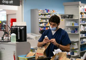 Pharmacy technician Keenan Becker fills prescriptions at a CVS in Mesa on Aug. 27, 2021. CVS Health plans to hire 25,000 people nationally during a one-day virtual event, including 600 in Arizona.