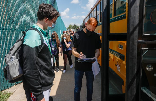Josiah Majerus, who plans bus routes but is chipping in to drive a bus, checks students onto the bus at the end of the day at Parkview High School on Thursday, Aug. 27, 2021.